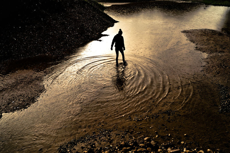 High angle view of silhouette person walking on puddle in field