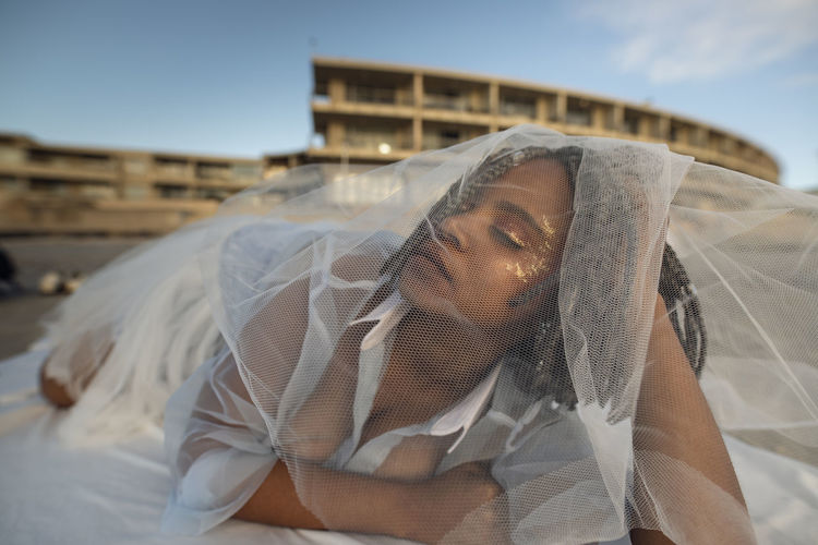 Young Woman In Tulle Netting Lying Outdoors