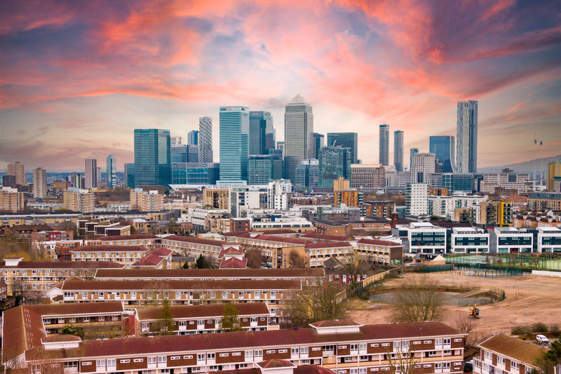 High angle view of buildings in canary wharf against sky during sunset