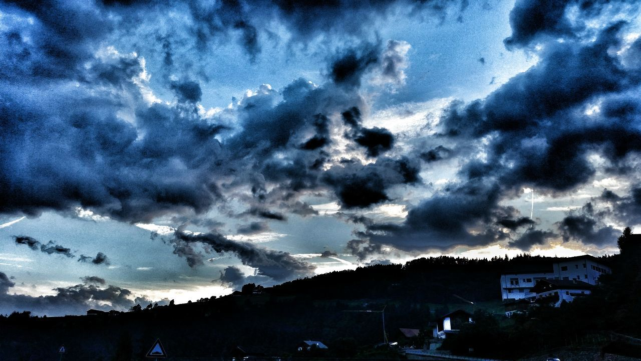 cloud - sky, sky, dramatic sky, building exterior, built structure, weather, architecture, outdoors, silhouette, no people, storm cloud, house, nature, scenics, low angle view, beauty in nature, sunset, tree, landscape, day, thunderstorm, mountain, city