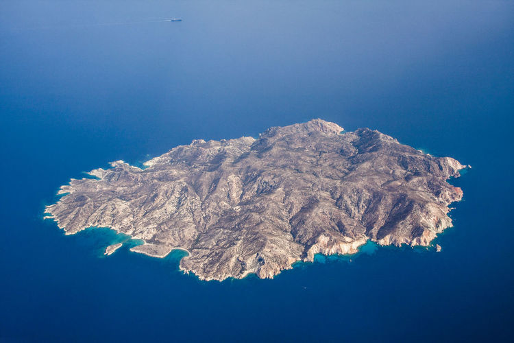 Aerial view of sea and mountain against blue sky