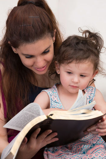Close-up of mother reading book with daughter
