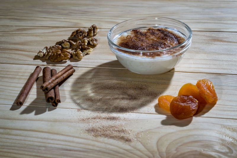 Creamy rice pudding with cinnamon sticks, walnuts and dried apricots on a wooden table Apricots Pudding Rice Cinnamon Dried Food Food And Drink Freshness High Angle View Indoors  No People Ready-to-eat Sutlija Sutlijas Sweet Food Table Wallnuts Wood - Material