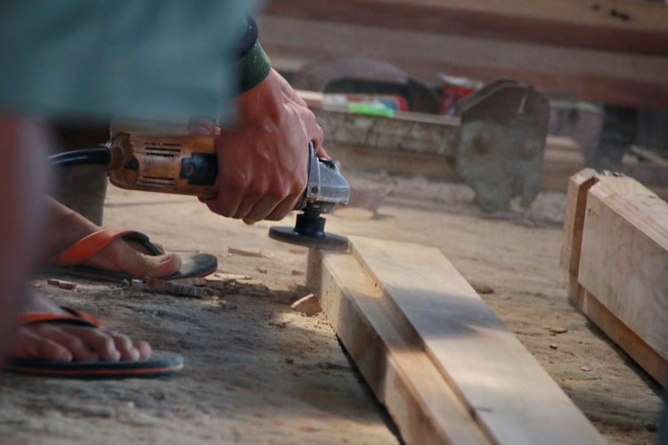 Low section of man holding work tool on plank