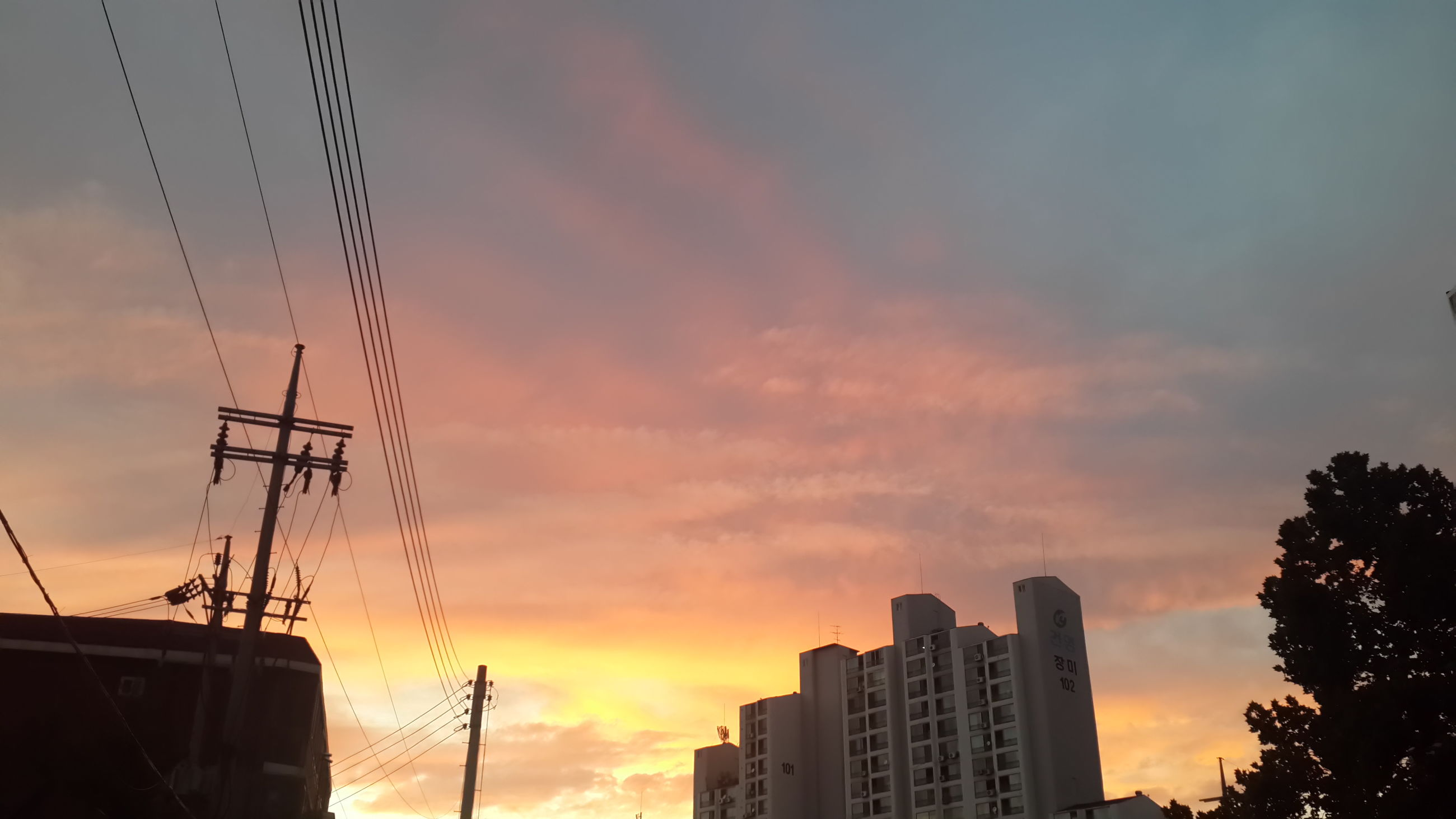 sunset, building exterior, architecture, low angle view, built structure, sky, silhouette, orange color, cloud - sky, power line, city, building, outdoors, cloud, cable, electricity pylon, no people, connection, residential building, high section
