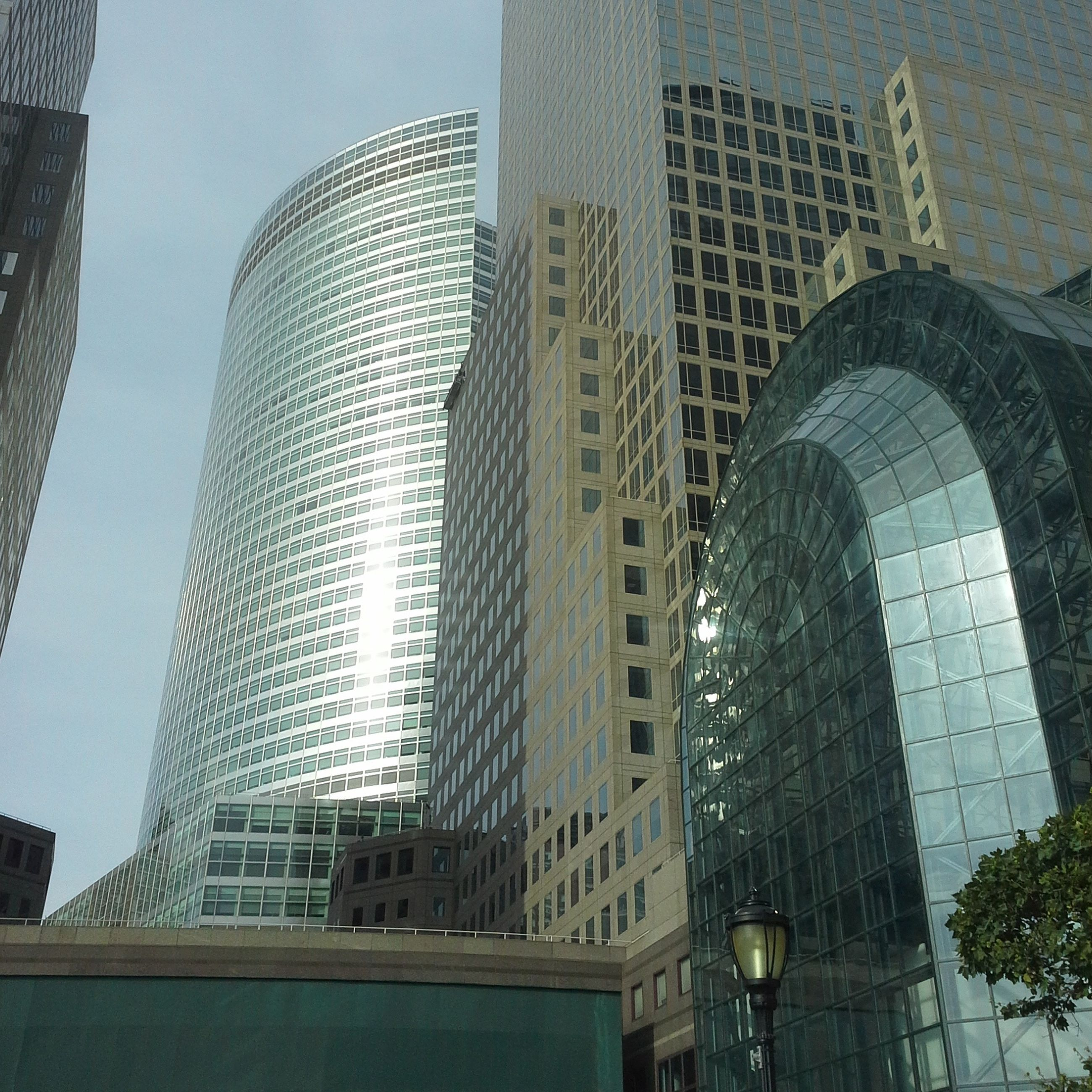 architecture, built structure, building exterior, modern, city, skyscraper, office building, low angle view, tall - high, tower, glass - material, building, capital cities, sky, reflection, tree, city life, clear sky, travel destinations, day