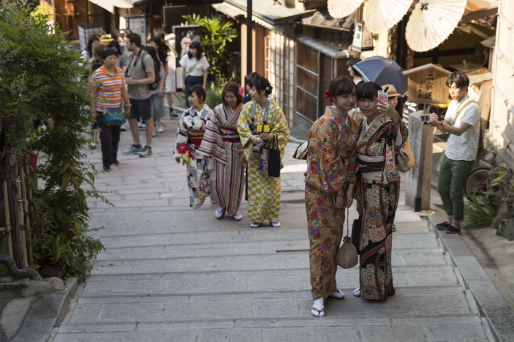 View down on one of the most popular streets in the higashiyama district old town of Kyoto. Female tourists wear traditional japanese kimono and pose for selfies and photos. Picture taken in May 2016. City Life City Street Japan Japan Photography Japanese Culture Japanese Style Tourist Tourist Attraction  Travel Photography Trip Beautiful Woman Candid Girls Higashiyama Kimono Kyoto Outdoors People Posing Posing For The Camera Real Life Real People Selfie Walking Women
