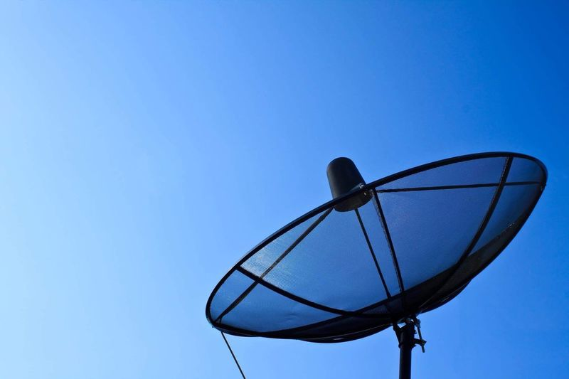 Satellite Technology Global Communications Clear Sky Communication Satellite Dish Connection Blue Low Angle View Copy Space Day Antenna - Aerial Telecommunications Equipment Wireless Technology No People Outdoors Built Structure Sky Nature