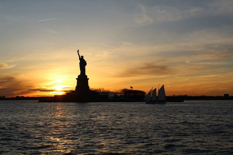 Liberty Statue Statue City Urban Skyline Silhouette Freedom Female Likeness Historic Icon Symbol Waterfront Human Representation Calm Boat Flaming Torch Wake - Water