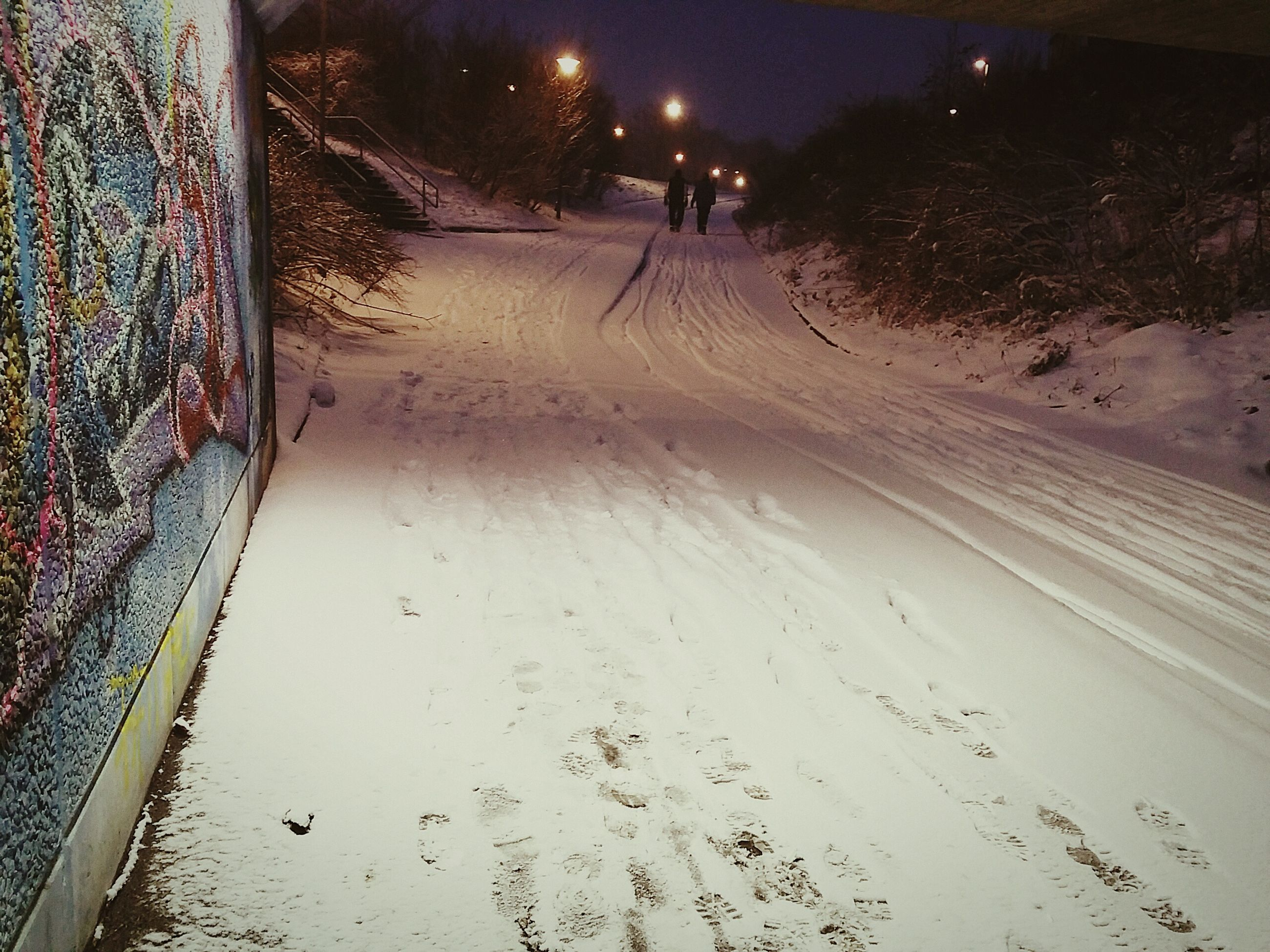 the way forward, snow, night, winter, illuminated, cold temperature, season, street, road, street light, diminishing perspective, high angle view, weather, footprint, transportation, incidental people, outdoors, vanishing point, sand, covering