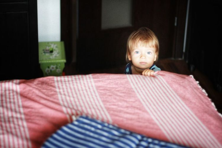 Portrait of cute boy with blonde hair and blue eyes sitting at home near bed