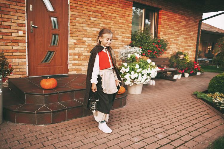 Full length of girl standing by flowering plants against house