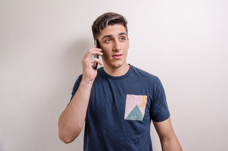 Portrait of young man using smart phone against white background