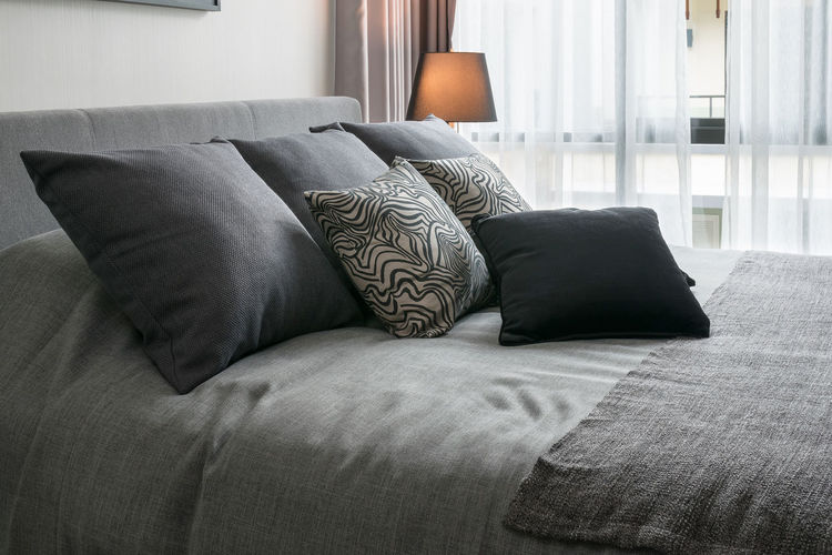 stylish bedroom interior design with black patterned pillows on bed and decorative table lamp. Absence Architecture Bed Bedroom Building Comfortable Cozy Curtain Cushion Day Domestic Room Furniture Home Interior Home Showcase Interior Indoors  Lifestyles Luxury No People Pillow Relaxation Sofa Stuffed