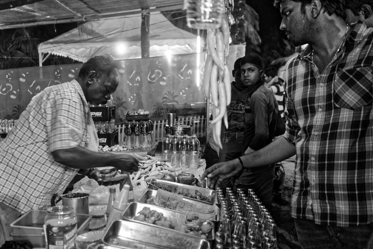 Fried food stall at a street fair Checkered Shirt Cooking,customers,fried Food, Peppersstall,cook,buying Food, Men,India, Night Time,halogen Lights Food Stall Local Food, Spicy Food Tasty Dishes