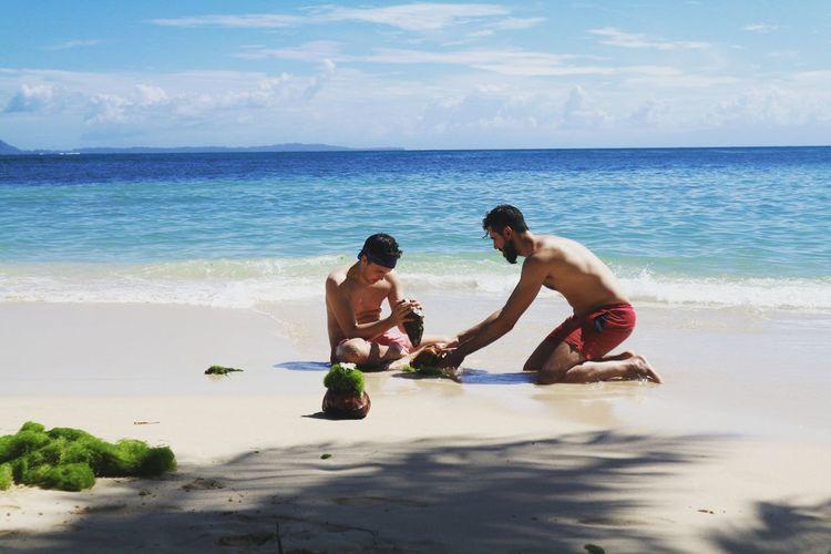 Shirtless men breaking seashell at beach against sky
