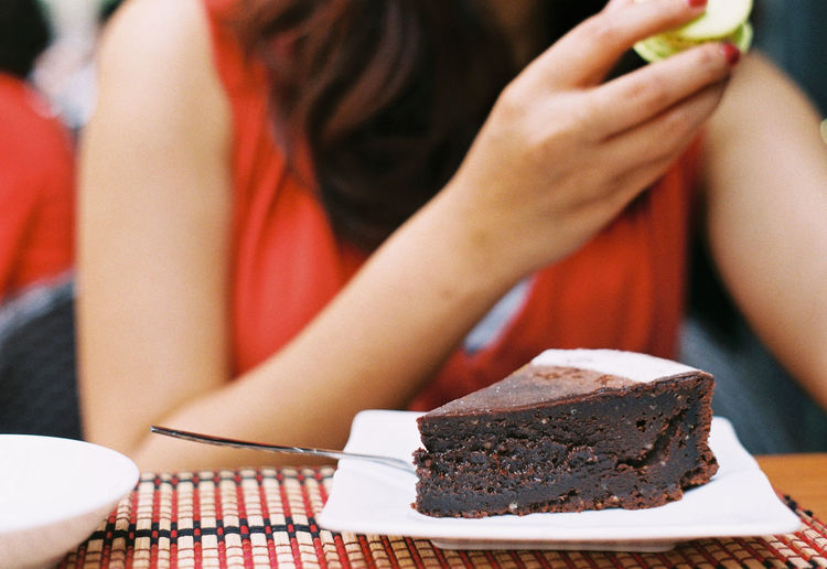 Midsection of woman with chocolate cake slice served in plate at restaurant