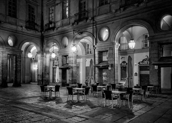 Empty chairs and tables in illuminated building at night