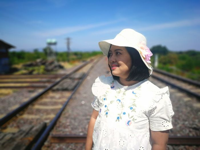 Mid adult woman standing on railroad track against sky
