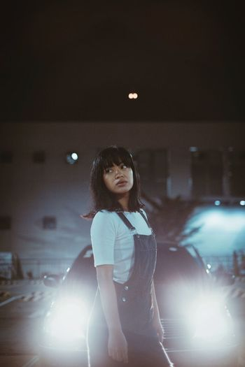 Portrait of young woman outdoors at night