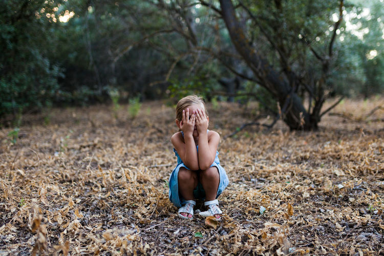 Girl covering face while crouching in forest