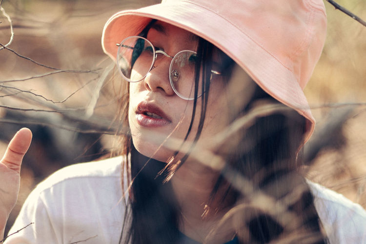 Close-up of young woman wearing hat outdoors