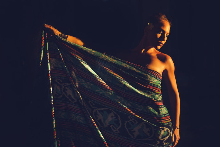 Girl wrapped in Indonesian fabric Bali Batik INDONESIA Beautiful Woman Black Background Fabric Fashion Fashion Model Half Profile Love Yourself One Person Shadows Standing Young Adult Inner Power The Fashion Photographer - 2018 EyeEm Awards Urban Fashion Jungle HUAWEI Photo Award: After Dark