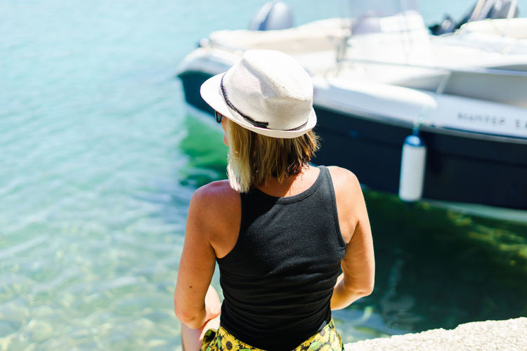 Rear view of woman sitting at sea
