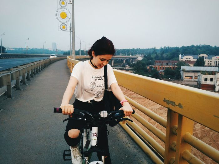 Woman Riding Bicycle On Bridge Against Clear Sky