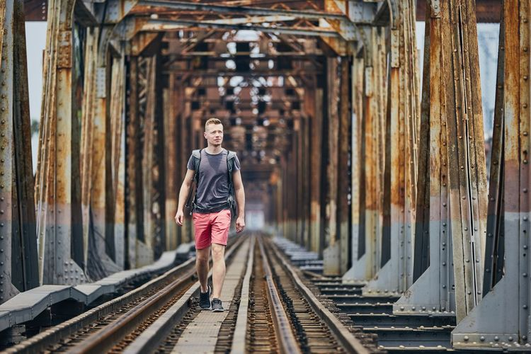 Man walking on railway bridge