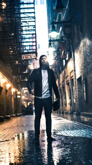 Full length of man standing on cobbled street against illuminated buildings