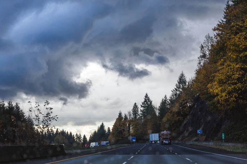 Dark clouds moving above traffic in the Pacific Northwest USA. Perspectives On Nature Beauty In Nature Car Cloud - Sky Day Land Vehicle Mountain Nature No People Outdoors Road Scenics Sky The Way Forward Tranquility Transportation Tree