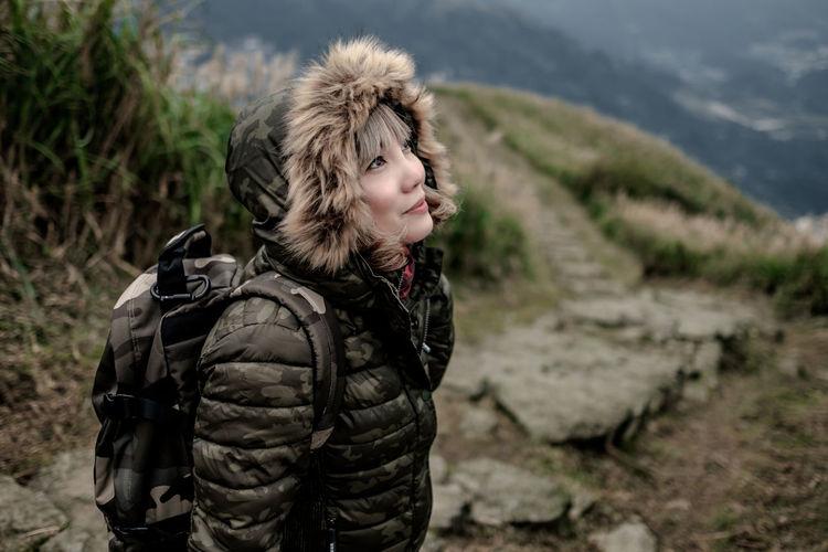 Woman looking at sky at top of keelung mountain, taipei, taiwan.