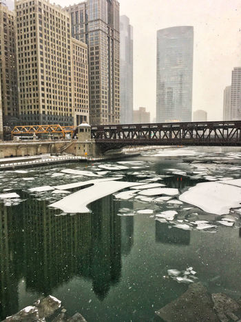 Reflections of surrounding cityscape in the Chicago River, which is filled with ice chunks on a frigid day. Waysofseeing Chicago River Downtown Chicago Winter Architecture Bridge - Man Made Structure Building Exterior Buildings Built Structure City Cityscape Cold Temperature Day Frigid Temps Modern No People Outdoors Refelctions River Sky Skyscraper Snow Snowfall Tower Urban Skyline Water