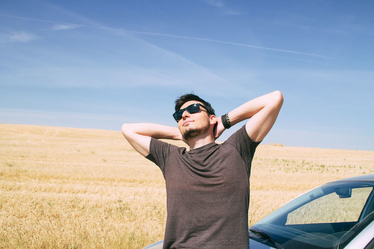 Smiling man wearing sunglasses while leaning on car against sky