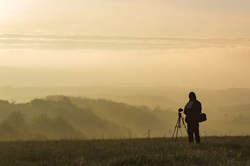 Rear View Of Photographer Standing On Field Against Sky At Morning