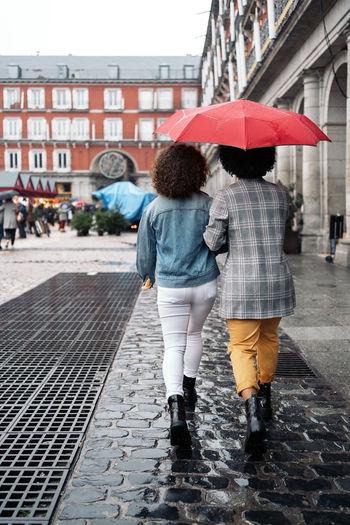Rear view of woman walking on wet street during rainy season