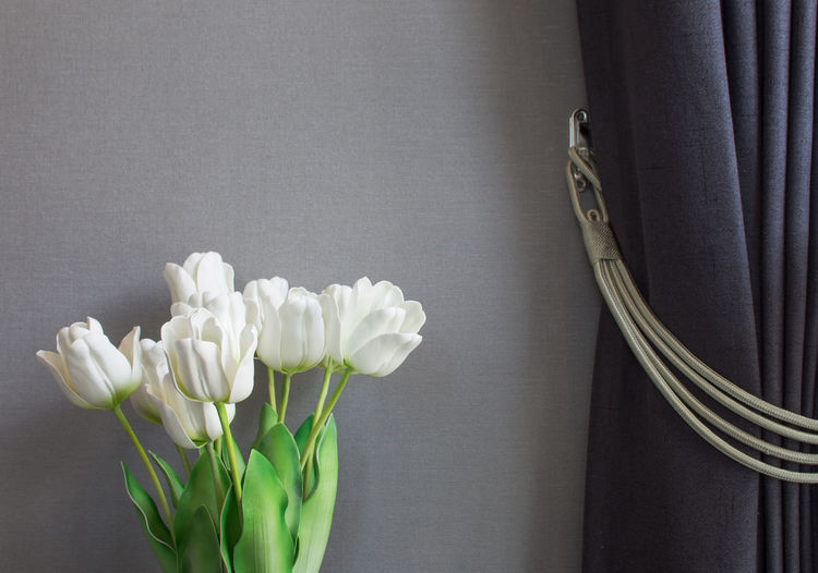 The fake tulips are made of plastic, decorated in gray walls with dark gray curtains that are gathered with silver threads on the sides. Artificial Flower EyeEm Selects Green Color Beauty In Nature Close-up Copy Space Curtain Decoration Flower Flower Arrangement Flowering Plant Fragility Freshness Gray Graywall Home Interior Indoors  Nature No People Petal Plant Still Life Studio Shot Table White Color