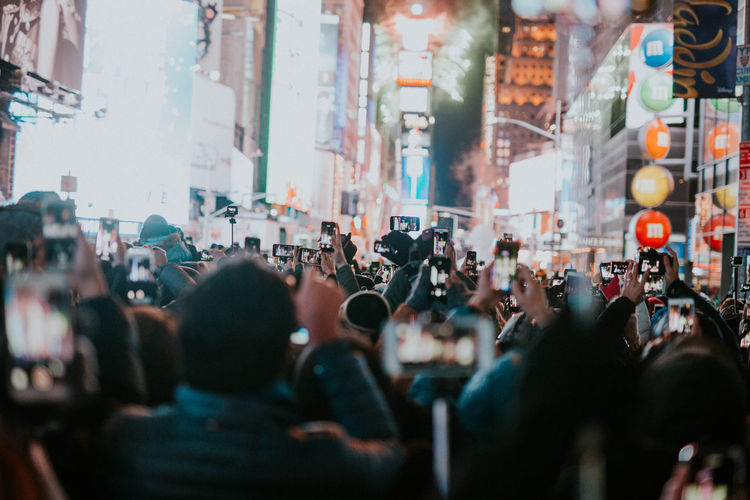 Crowd photographing on illuminated street at night