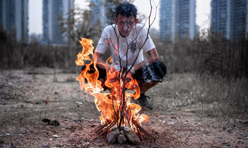 Portrait of young man crouching by fire on field