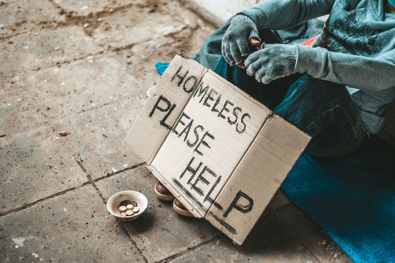 Low section of homeless man sitting on street