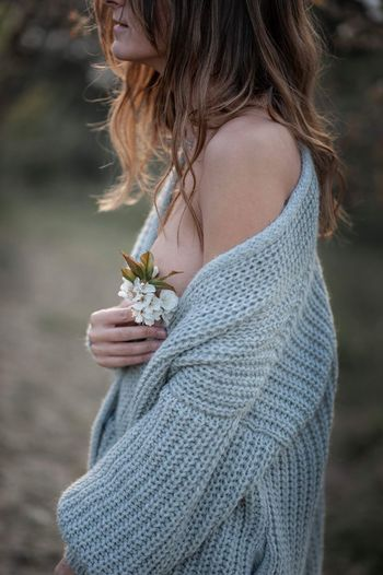 Midsection of woman wearing sweater while standing outdoors