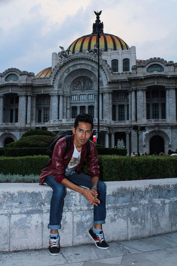 Portrait Of Man Sitting On Retaining Wall Against Palacio De Bellas Artes