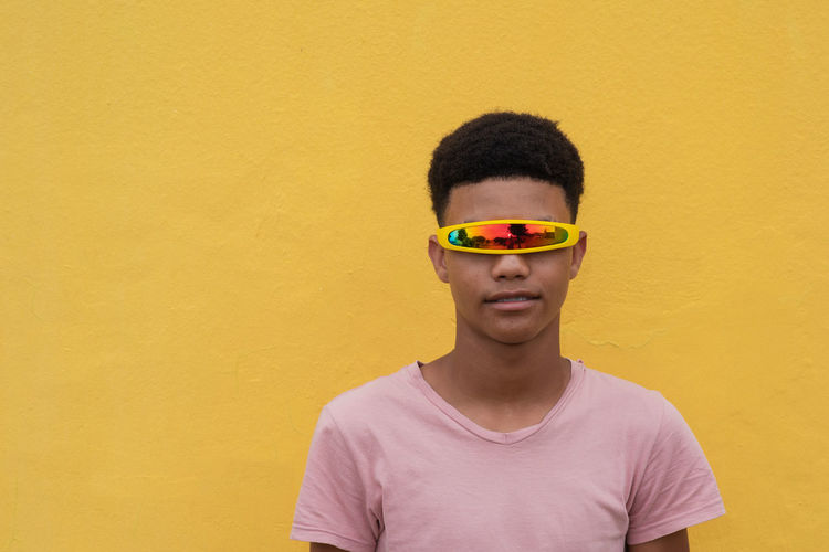 Portrait of teenage boy wearing colorful sunglasses standing against yellow wall