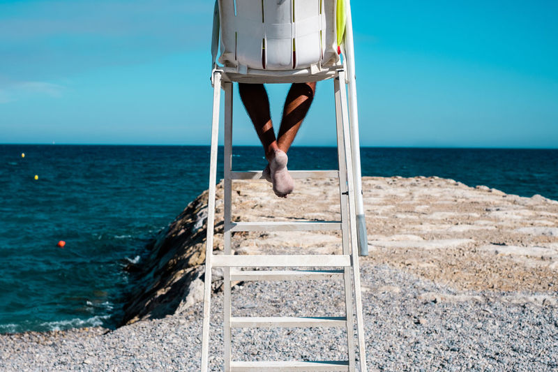 Low section of man sitting on lifeguard chair at beach