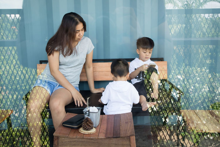 Mother and son of her sit on a chair with her father's shadow photographed. Adult Boys Casual Clothing Child Childhood Daughter Family Females Girls Group Of People Males  Men Mother Offspring Parent Sibling Sister Son Three Quarter Length Togetherness Women