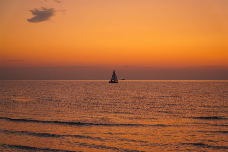 Silhouette sailboat in sea against orange sky