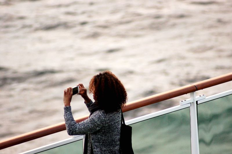Side view of woman photographing sea