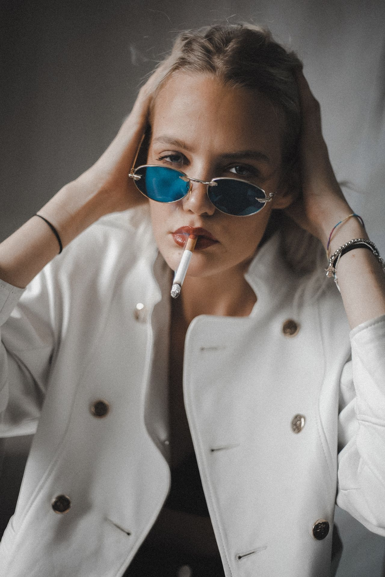 Portrait of woman wearing sunglasses while smoking cigarette