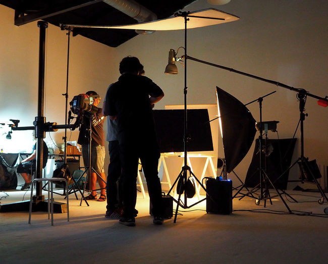 Silhouette of people working in production studio for shooting or recording by digital camera and lighting set. Arts Culture And Entertainment Men Studio Musical Equipment Real People Indoors  Musical Instrument Standing Music People Lighting Equipment Equipment Artist Two People Occupation Technology Musician Stage Photographic Equipment Light - Natural Phenomenon Entertainment Occupation Photo Shoot Rock Music Concert Photographer Studio; Video; Shoot; Film; Photo; Camera; Photographer; Shooting; Equipment; Professional; Photography; Production; Tv; Work; Movie; Set; Digital; Background; White; Television; Light; People; Industry; Crew; Flash; Man; Director; Spotlight; Lamp; Making
